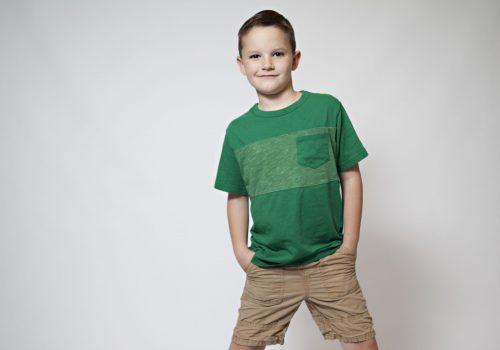 boy-in-green-shirt-on-white-background-poses-for-a-V78V99E