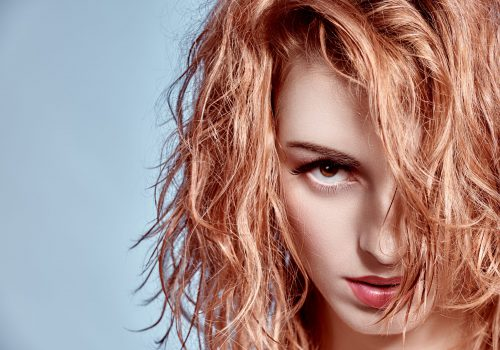 Beauty portrait woman with wet wavy hair. Playful sexy redhead model, natural makeup, fashion.Sensual attractive girl provocative looks, long eyelashes, copyspace, blue.People face closeup. Confidence